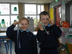 Alex and Aoife proudly show off their medals won for running and football.